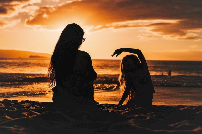 夕日の輝く浜辺にいる母子