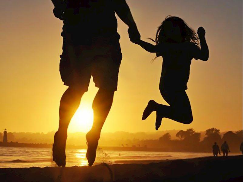 夕焼けの海岸でジャンプする親子